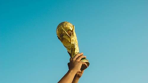 Puchar trzymany wwyciągniętych wgórę dłoniach
